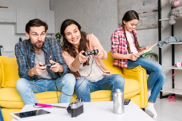 Pais jogando videogame e filha lê