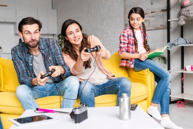 Pais jogando videogame e filha olha para eles
