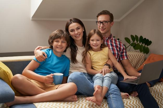 Pais jovens alegres e seus filhos sentados no sofá da sala de estar sorrindo para a câmera
