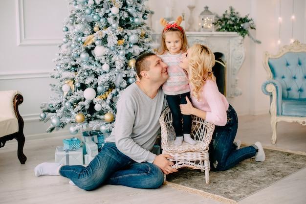 Pais jovens brincando com um bebê perto da árvore de natal
