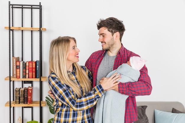 Pais jovens, com, bebê, olhando um ao outro