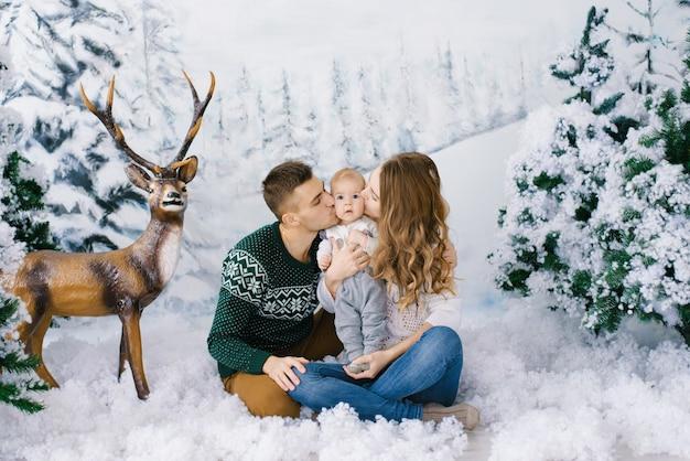 Pais jovens com um bebê beijam o bebê nas bochechas e sentados na neve artificial