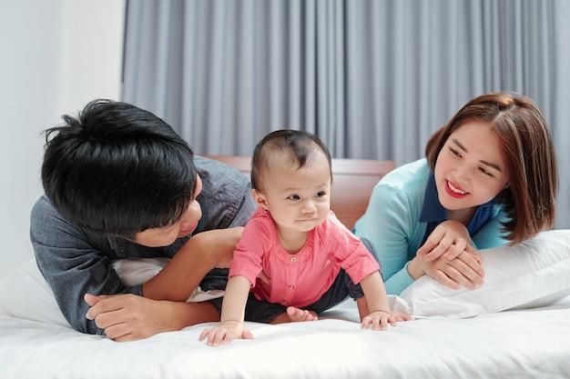 Pais jovens e felizes, deitados na cama olhando para sua filhinha engatinhando
