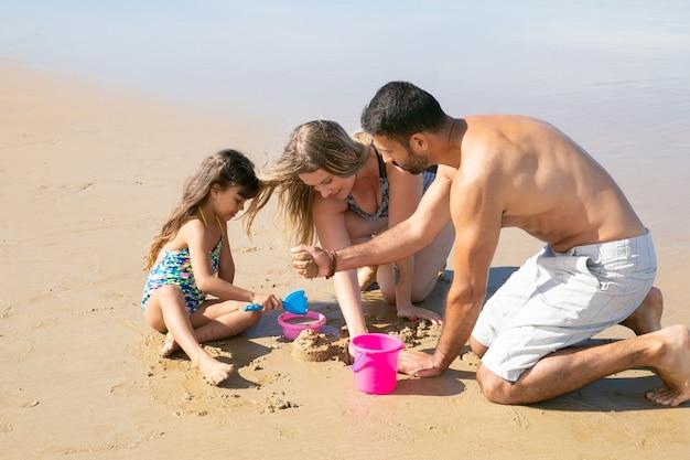 Pais jovens e uma doce menina brincando juntos na praia, construindo construções de areia com uma pá de brinquedo, balde e tigela