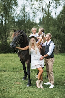 Pais jovens felizes com suas duas filhas bonitas, sentados no cavalo, no rancho