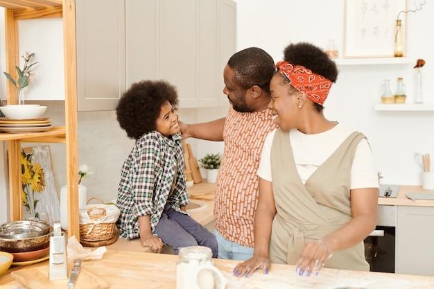 Pais jovens felizes e filho pequeno cozinhando juntos