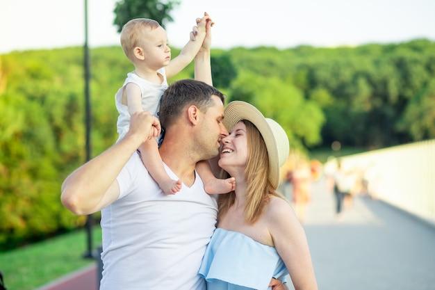 Pais jovens felizes, mamãe e papai com seu filho bebê estão passeando no parque no verão, se divertindo, sorrindo e se beijando