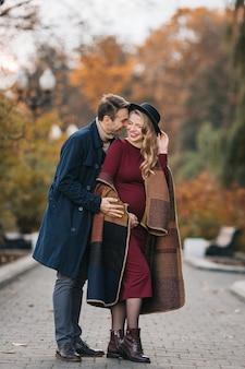 Pais jovens felizes, um homem elegante em uma capa de chuva e uma jovem grávida em um vestido vermelho e ...