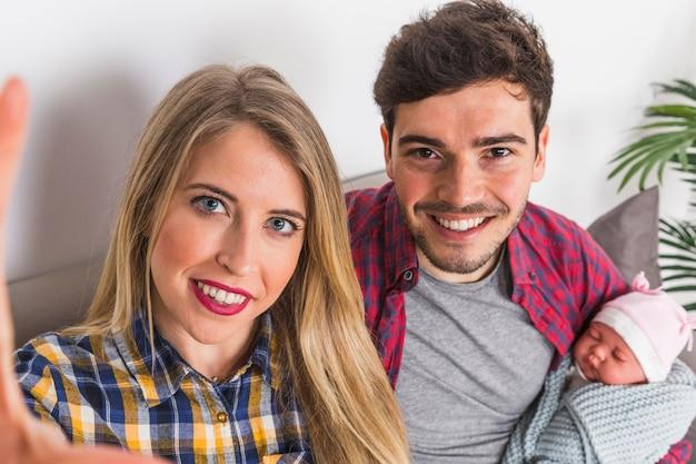 Pais jovens que tomam selfie com bebê