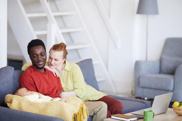Pais jovens sentados no sofá e olhando para o bebê enquanto ele dorme, eles sentados no sofá da sala de estar
