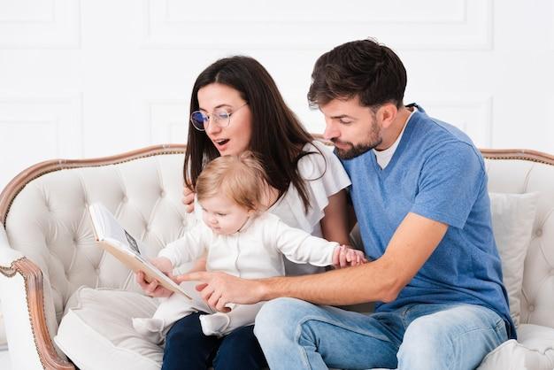 Pais lendo enquanto segura o bebê