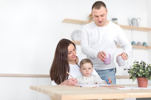 Pais na cozinha com criança