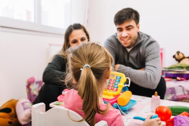 Pais, olhar, filha, tocando, brinquedos