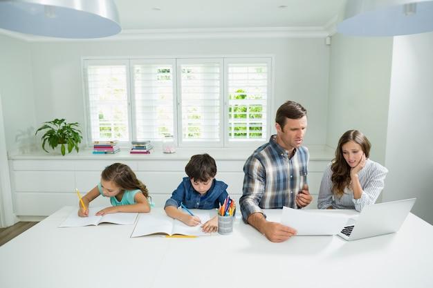 Pais que trabalham com laptop e crianças estudando na sala de estar