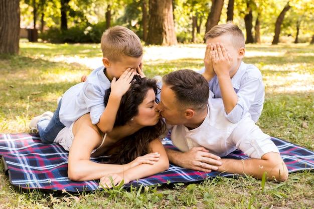 Pais se beijando enquanto as crianças cobrem os olhos