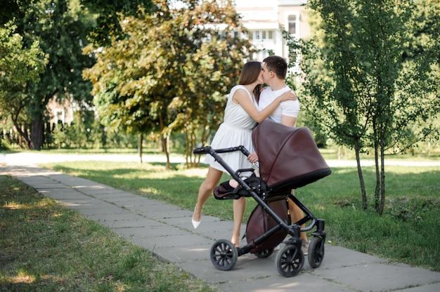 Pais se beijando perto de sua filha na carruagem de bebês