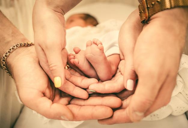 Pais, segurando, bebê, pés, em, seu, mãos