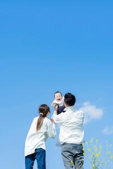 Pais segurando seu bebê bem alto sob o céu azul