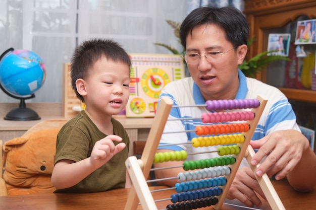 Pais sentados ensinando em casa com uma criança de 4 anos, pai e filho se divertindo, aprendem a contar usando o ábaco em casa, usam um ábaco para ensinar matemática para crianças pequenas