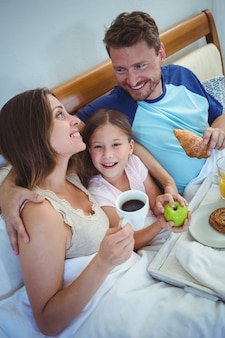 Pais sentados na cama com a filha e tomando café da manhã