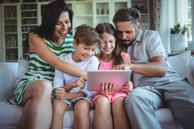 Pais sentados no sofá com seus filhos e usando tablet digital na sala de estar