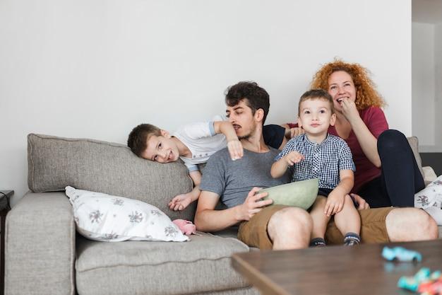 Pais, sentando, com, seu, crianças, olhando televisão