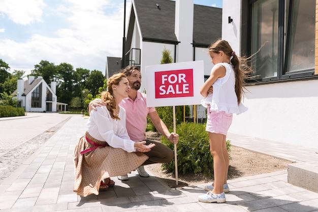 Pais simpáticos e agradáveis olhando para a filha enquanto perguntam o que ela não gosta na casa