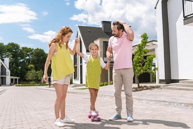 Pais simpáticos e atenciosos segurando as mãos da filha enquanto a ajudam a andar de skate