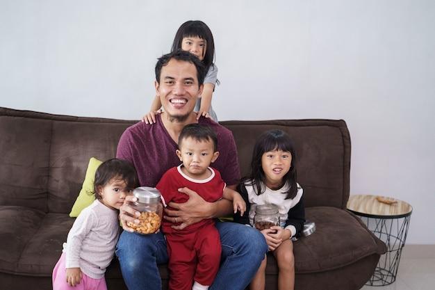 Pais solteiros de um pai com 4 filhos sentados em um sofá em casa