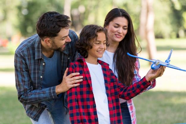 Pais sorridentes e criança brincando juntos com um avião ao ar livre