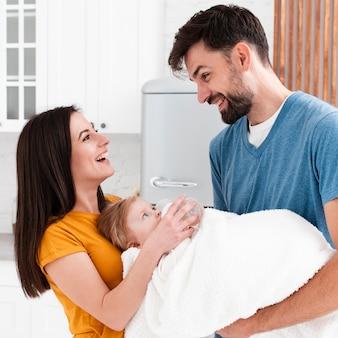 Pais sorridentes, segurando bebê