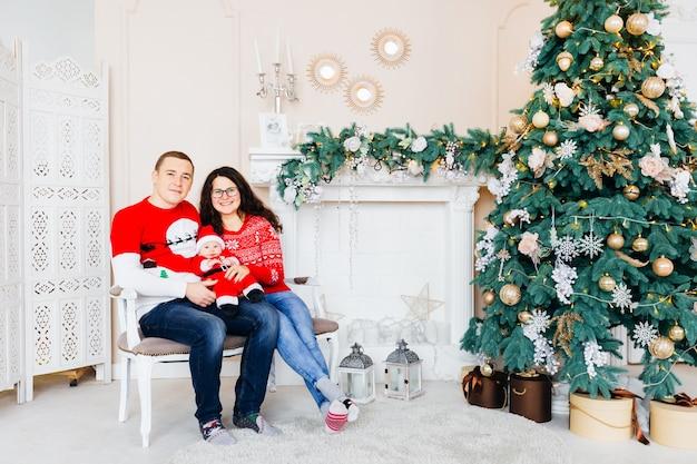 Pais sorridentes sentam no sofá e olham para as lentes da câmera e entre eles um filho pequeno em uma roupa de papai noel na sala com árvore de natal e lareira