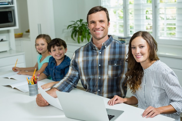 Pais sorridentes trabalhando com laptop e crianças estudando na sala de estar em casa