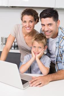 Pais sorridentes usando laptop com seu filho