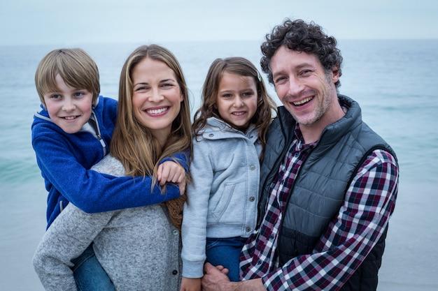 Pais sorrindo enquanto carregava filhos na costa do mar