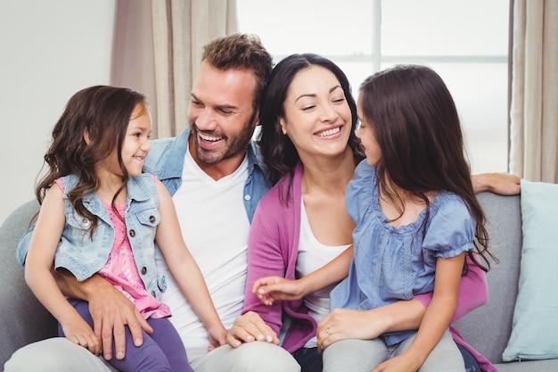 Pais sorrindo enquanto está sentado com as filhas no sofá