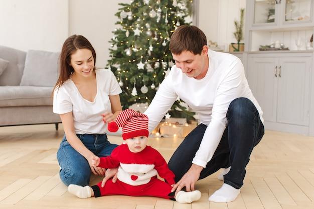 Pais, tocando, com, bebê, perto, árvore natal