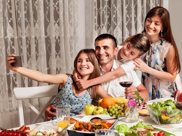 Pais tomando selfie com crianças na mesa de jantar