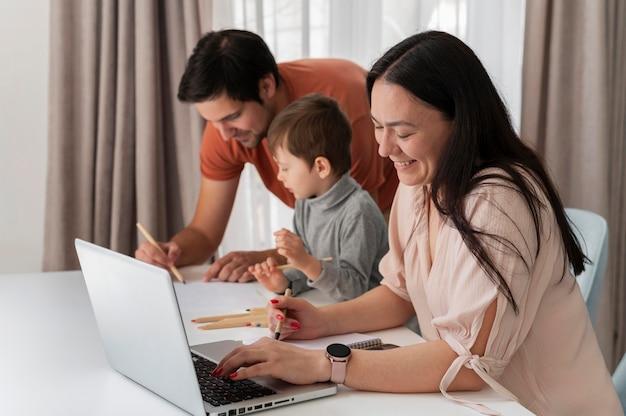 Pais trabalhando em casa com filho