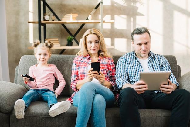 Pais, usando, tablete digital, e, telefone móvel, enquanto, filha, olhando televisão