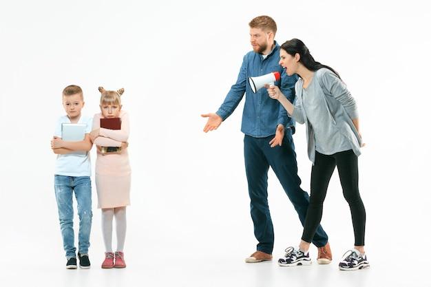 Pais zangados repreendendo seus filhos - filho e filha em casa. foto de estúdio de família emocional. emoções humanas, infância, problemas, conflito, vida doméstica, conceito de relacionamento