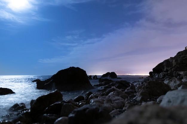 Paisagem à beira-mar no meio da noite com pedras
