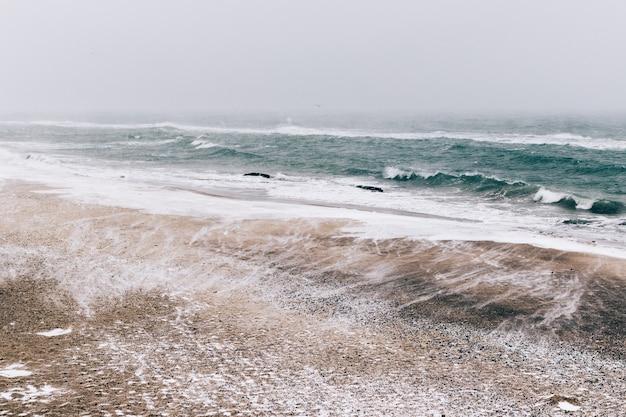 Paisagem abstrata de inverno da praia durante uma queda de neve e vento