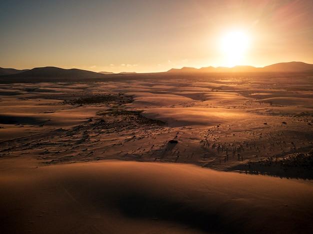 Paisagem aérea cênica de deserto arenoso com dunas e pôr do sol no horizonte