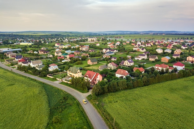 Paisagem aérea da pequena cidade ou vila com fileiras de casas residenciais e árvores verdes.
