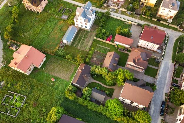 Paisagem aérea de uma pequena cidade ou vila com fileiras de casas residenciais e árvores verdes.