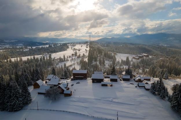 Paisagem aérea do inverno com pequenas casas de aldeia entre floresta coberta de neve em montanhas frias à noite.