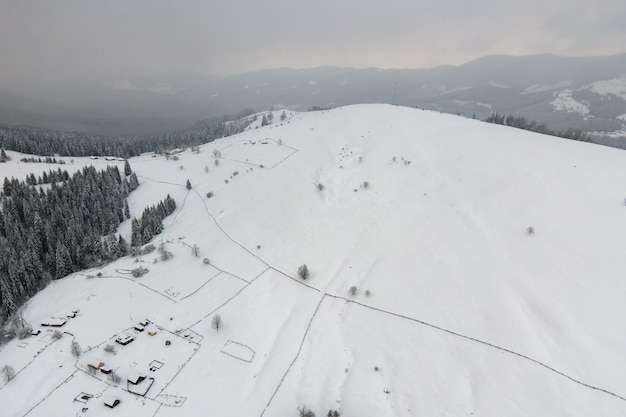 Paisagem aérea do inverno com pequenas casas rurais entre floresta coberta de neve nas montanhas frias.