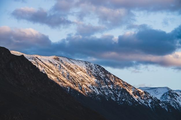 Paisagem alpina atmosférica ao cume da montanha de neve no pôr do sol. neve brilha em luz dourada no pico da montanha. lindo topo nevado brilhante. noite céu nublado. cenário maravilhoso em tons de ouro por do sol.