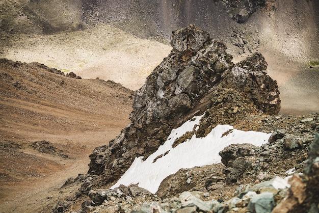 Paisagem alpina atmosférica com firn ou neve perto de um penhasco rochoso no fundo da parede de uma montanha em combe rocky hill